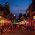 People walk along a street at night in New Orleans