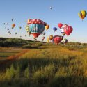Hot air balloons float over a grassy field at sunset in Albuquerque, New Mexico