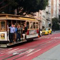 Trolley car with people holding onto the edge heading down a slight hill during the daytime in San Francisco