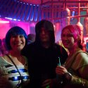 Two women and a man dressed in Starwars cosplay in a pink and blue bar.