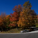 A car is parked along a curved roadway, lined with red and orange trees during Fall in Vermont
