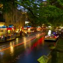Boats float along the San Antonio Riverwalk at night, illuminated by café lights