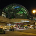 Indianapolis ArtsGarden glass dome lit up green at night.