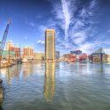 Buildings in Baltimore up against the shore line during the day under a blue sky