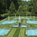 Bright blue ponds in a green garden with fountain