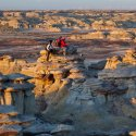 Two hikers sit on hills of rock in the Bisti Badlands in New Mexico