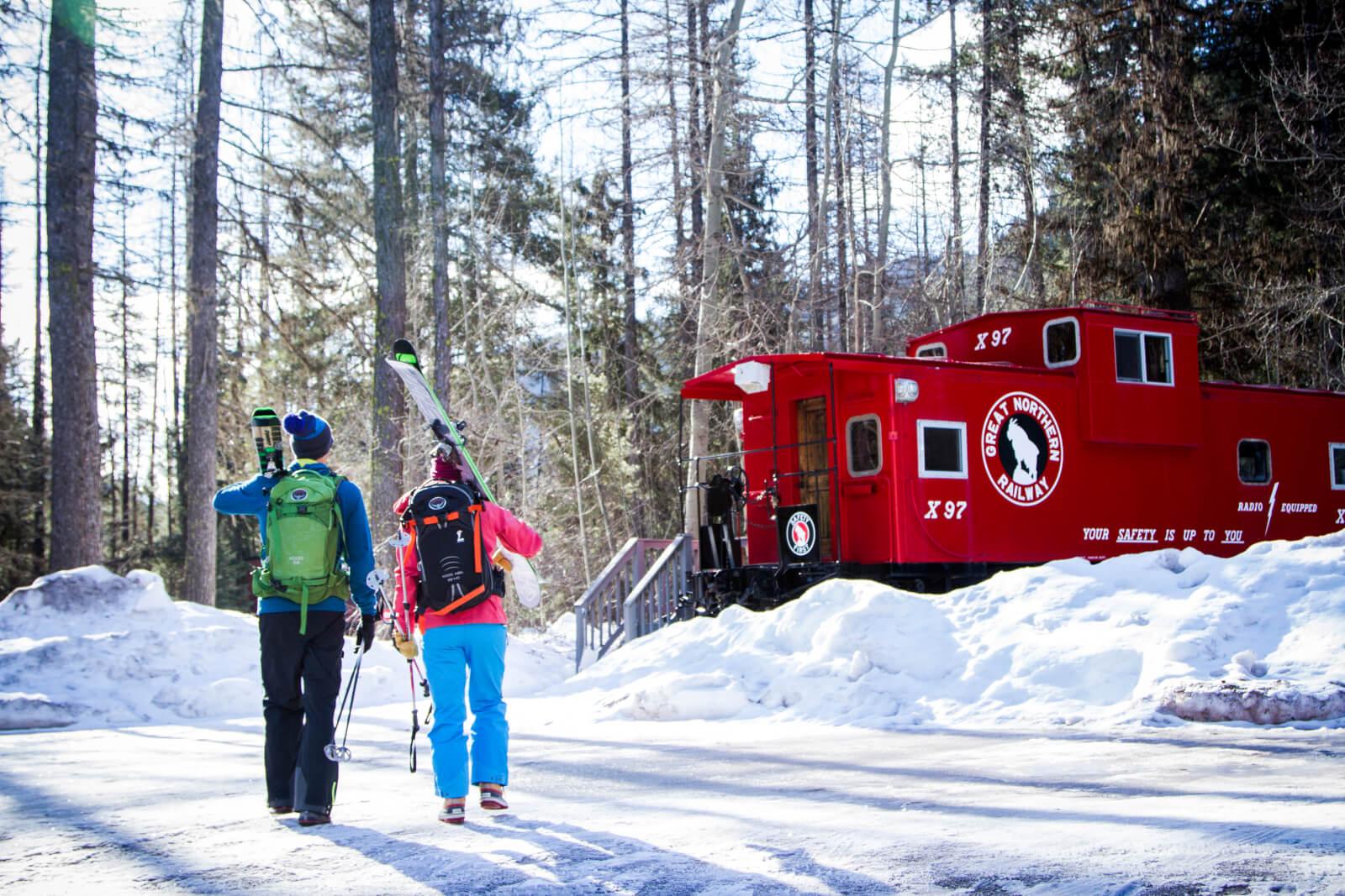 Two skiiers walking towards Izaak Walton Inn
