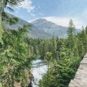 Photo of Glacier National Park, tall mountain peak and flowing water feature.