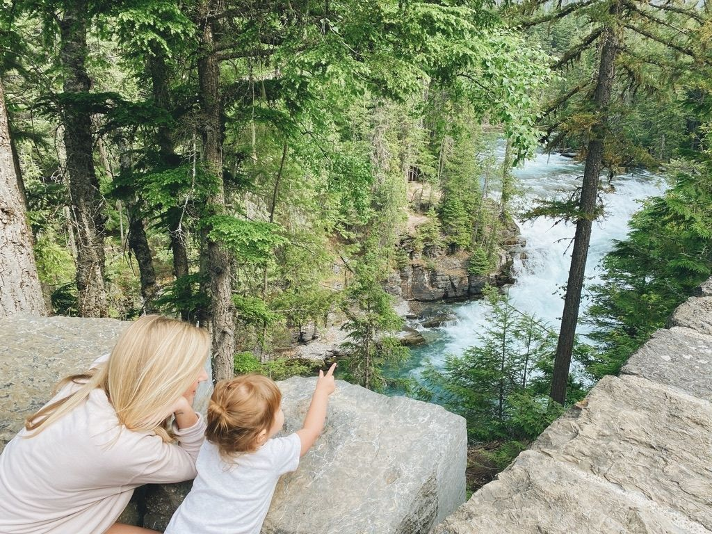 Blonde woman with toddler pointing at a river and forest in Glacier National Park.