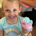 Youngest daughter, Charlotte smiles for the camera holding an ice cream cone with multicolor scoops in Branson Landing, Branson, Missouri.