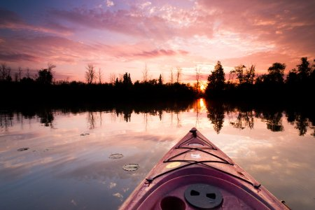 A kayak cuts through the water at sunset in Alpena County, Michigan.