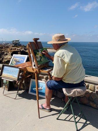 Artist Robert A. Higgins sitting seaside in San Diego, California, paintings images of the coast.