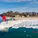 A paddleboarder floats along the ice-covered shore of Lake Michigan in the shadow of the iconic red South Pier Lighthouse in Charlevoix, Michigan.