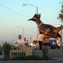 A man takes a photo of woman posing in front of a giant roadrunner statue, Paisano Pete Roadrunner, at sunset in Texas