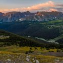 Grassy green hills and indigo mountains are seen at sunrise on Trail Ridge Road in Rocky Mountain National Park
