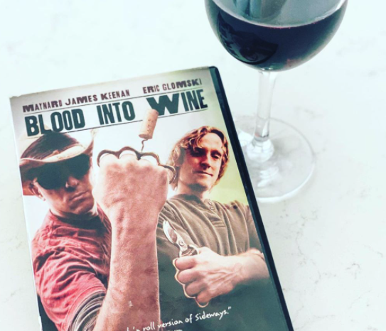 """A copy of the documentary """"Blood into Wine"""" with musician Maynard James Keenan on the cover and glass of wine from Caduceus Cellars sit side-by-side atop a marble table."""