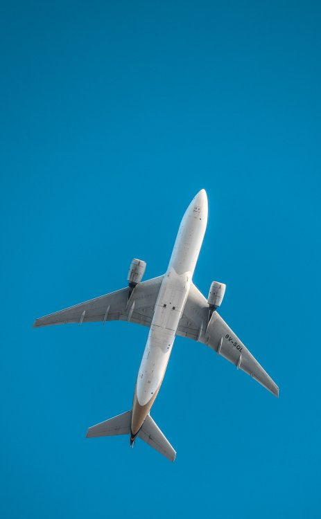 An airplane seen from below, passing overhead