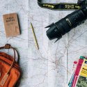 A camera, backpack, and stack of travel guides sit atop an open map.