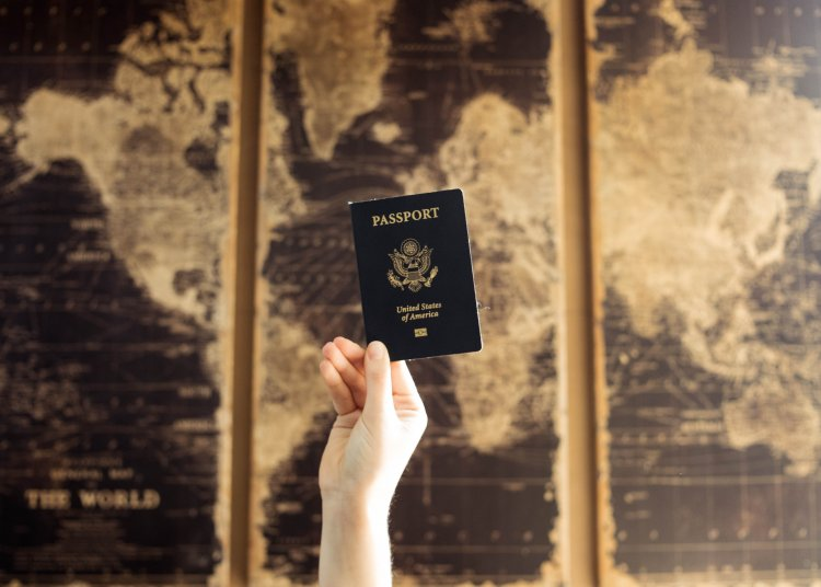 Passport held up in front of a map of the world