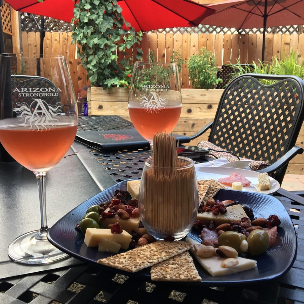 Two glasses of chilled wine sit adjacent to a charcuterie board on the patio of Arizona Stronghold Vineyards in Old Town Cottonwood, Arizona.