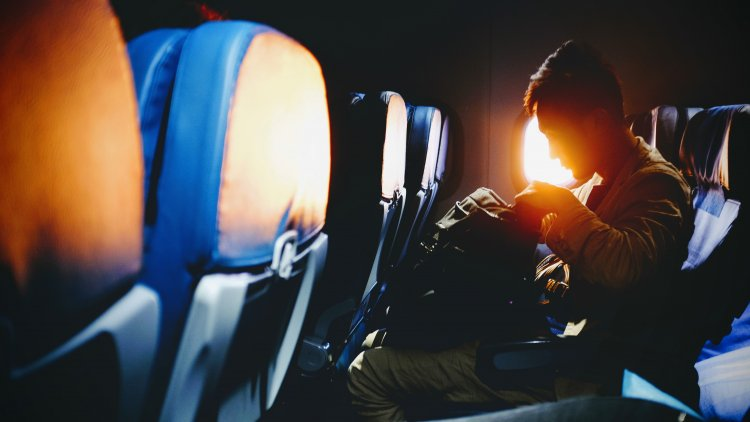 Man looking in his baggage on an airplane.