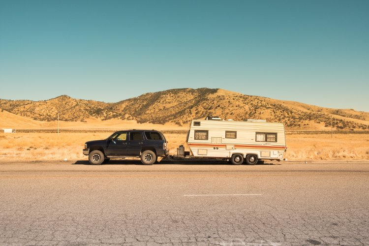Towable camper and SUV parked by the side of a desert road.
