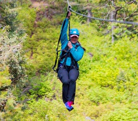 woman ziplining through a forest of trees at Tamarack Resort.