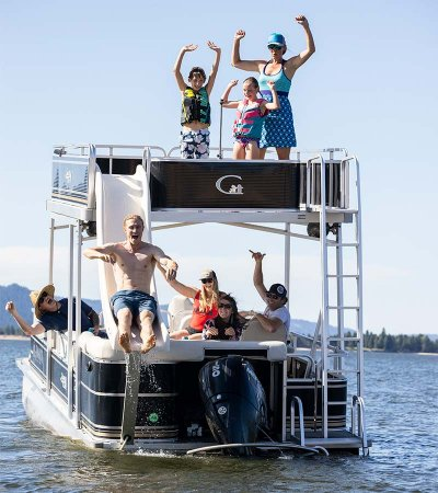 group of eight people riding a double decker pontoon boat on a lake and a man sliding down the boat's water slide at Tamarack Resort