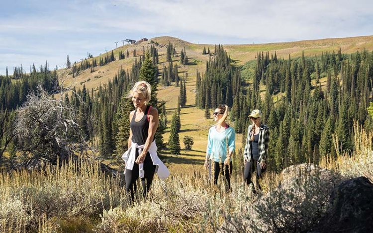 three women hiking at Tamarack Resort with a tree-covered hill in the background.