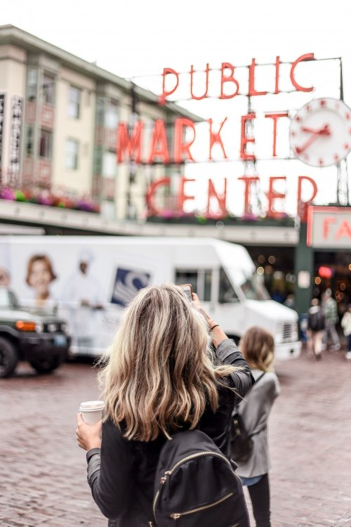 Woman, shot from behind, taking a photo of the Public Market Center sign in Seattle.