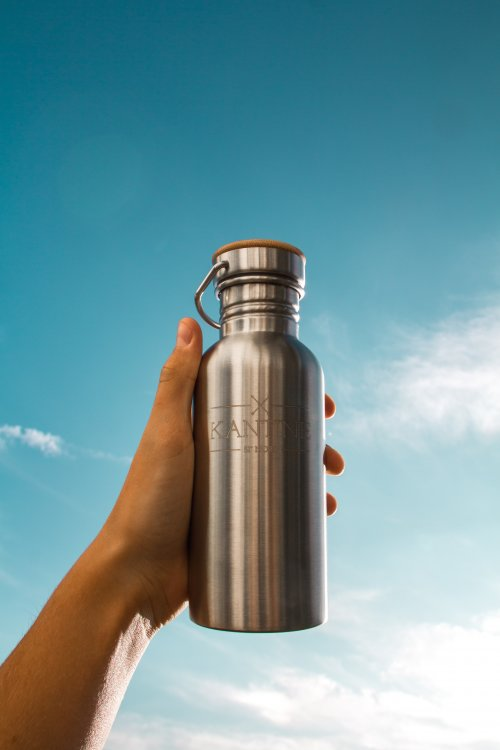 Image of a hand holding a water bottle up to the sky. Blue sky with Clouds.