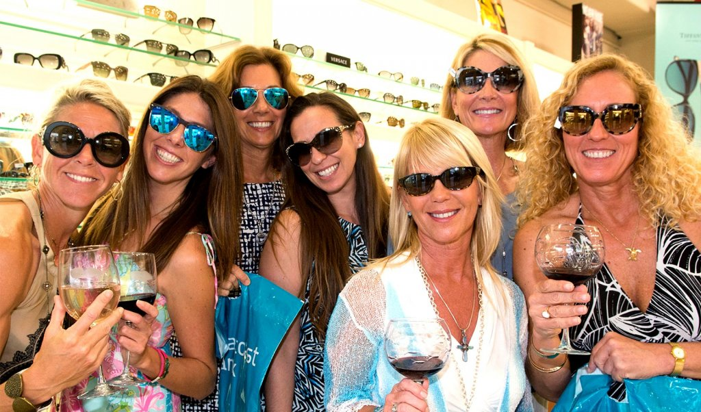 A group of women trying on sunglasses and drinking wine at a Martin County, Florida, shopping event