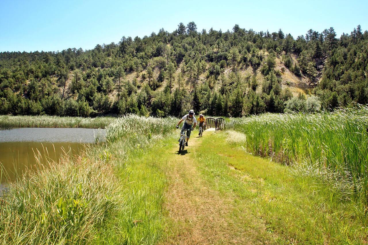 Two mountain bikers ride on a trail alongside water