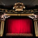 Broadway theatre stage with red draping and intricate gold chandelier and columns.