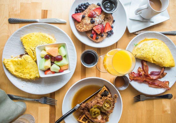 Breakfast food spread. Waffles, omelets and fruit.