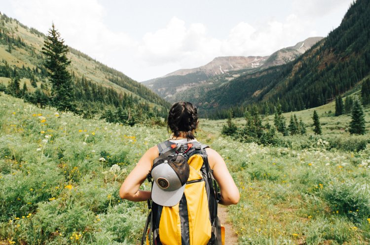 Woman seen from behind, with hiking gear, looking out across a valley.