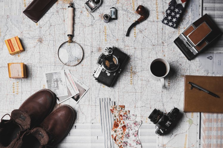 Top down view of a map covered in travel related equipment: Shoes, camera, notebook, etc.