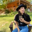 A patron of D.A. Ranch Lodge & Estate Vineyards in Cornville, Arizona sits outside the lodge drinking a glass of red wine, laughing.