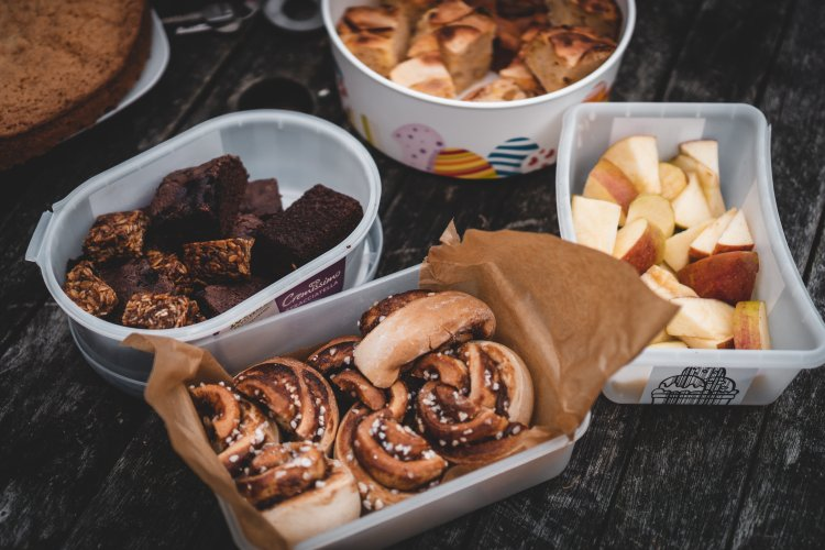 assorted snack mix including cinnamon rolls, brownies and apples.