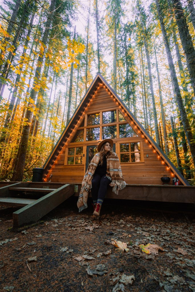 Photo of a women outside of a vacation rental house shaped like triangle in the woods.