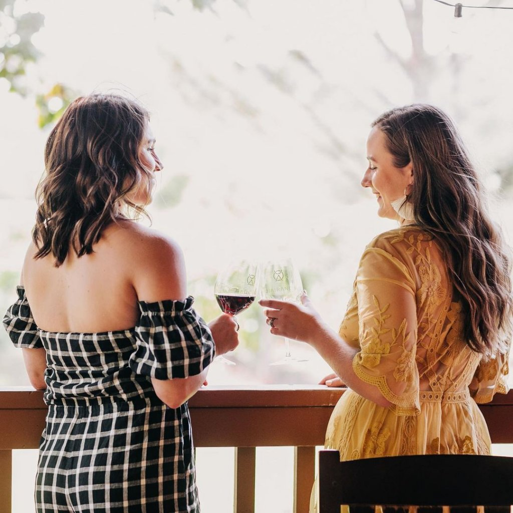 Two friends stand on the patio of D.A. Ranch Lodge & Estate Vineyards in Cornville, Arizona toasting with two glasses of wine.