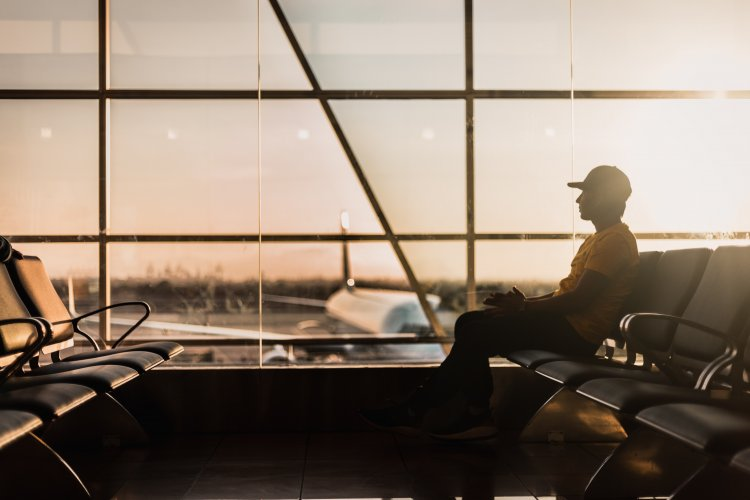 Man sitting in airport boarding area. A plane on the tarmac is visible in the background. Bright, warm tones and sunlight coming through a window.