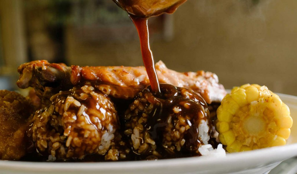 Plate lunch with rice, gravy, corn, and meat from a Lafayette, LA restaurant