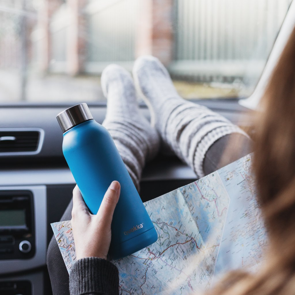 Women in passenger seat of car with legs on the dashboard, holding a map and a blue water bottle.