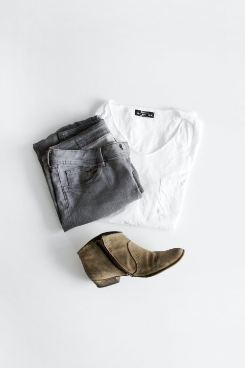 Grey pants, white shirt and earthen toned Shoe laid out on a bright background.