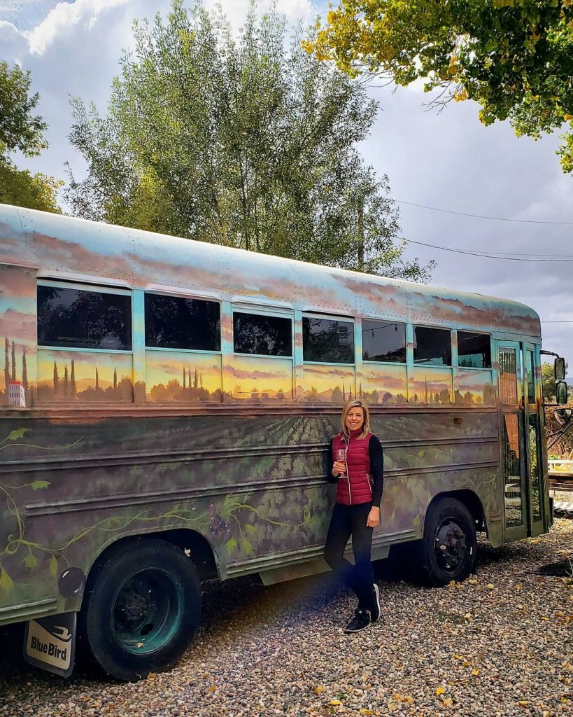 A patron of Clear Creek Vineyard & Winery in Camp Verde, Arizona, stands in front of bus painted to look like vineyards holding a glass of wine.