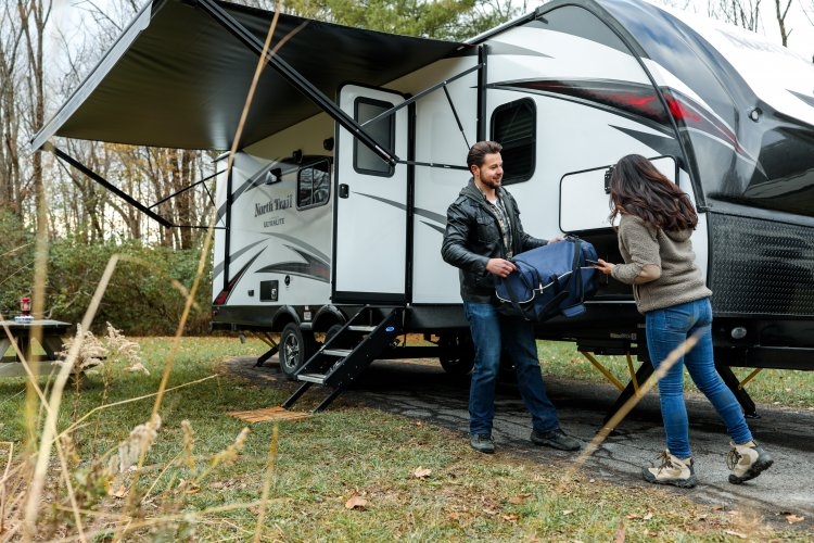 Couple standing outside of their RV with its awning extended.