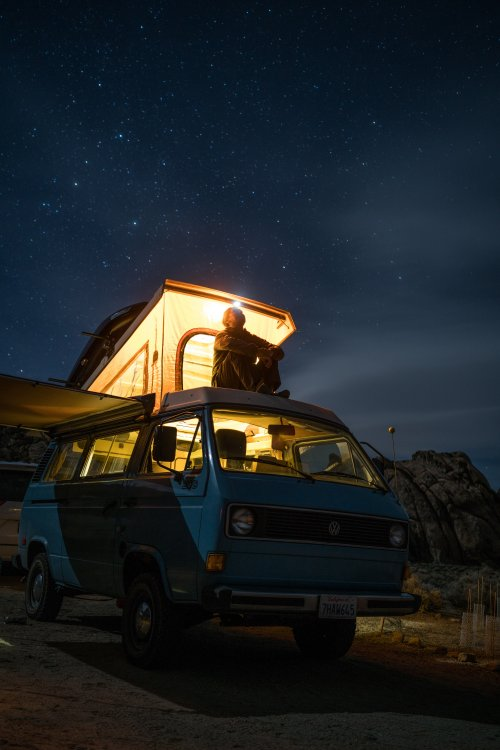 Man sitting on top of a camper van under cover of starlight