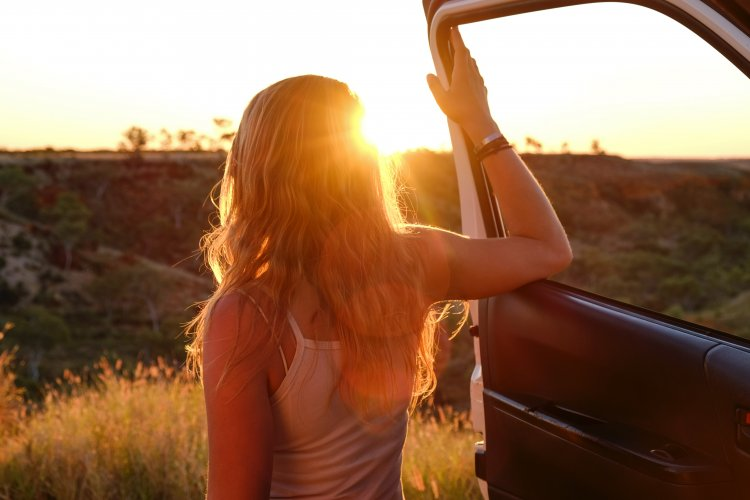 Woman standing in the door of her car looking out at the sun.