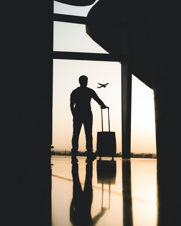 Man in silhouette with a suitcase looking out as a plane takes off in the distance